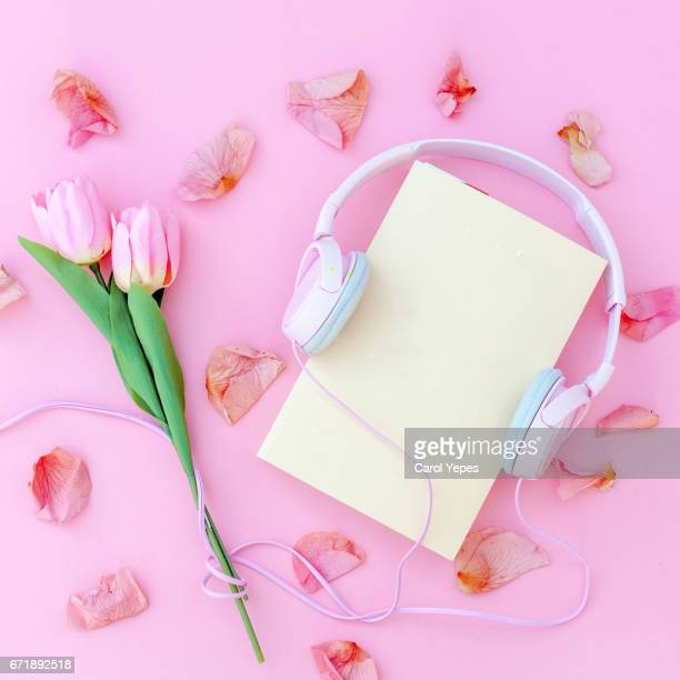 flat lay mockup book with headphones and tulips and petals.Pink background