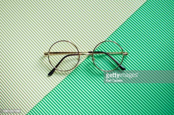 a flat lay of a pair of round-shaped eye glasses - pair stock pictures, royalty-free photos & images