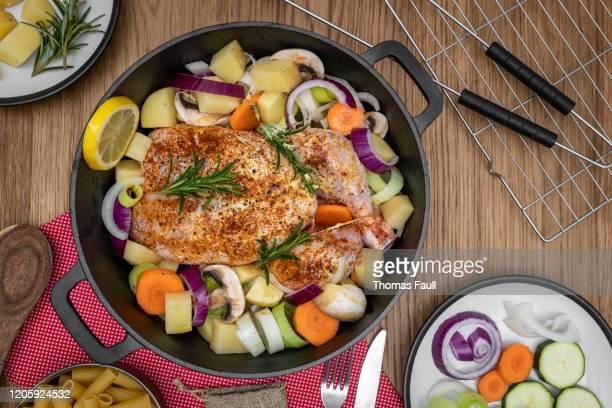 野菜とオランダのオーブンで鶏肉全体の平らなレイ - ダッチオーブン ストックフォトと画像