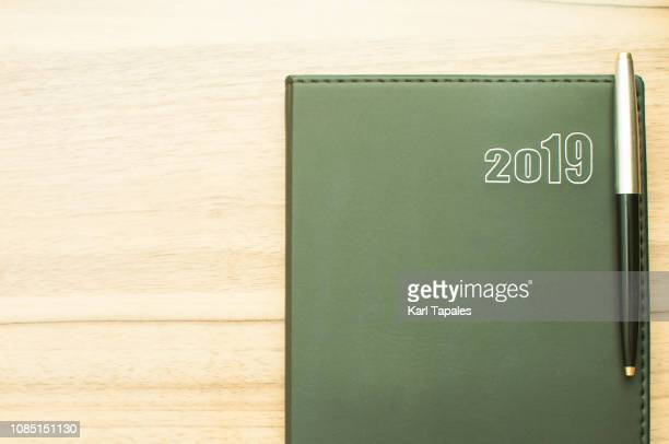 a flat lay of black 2019 personal organizer and a pen - march month stock pictures, royalty-free photos & images