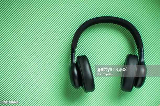 a flat lay of black pair of headphone - podcast stock-fotos und bilder