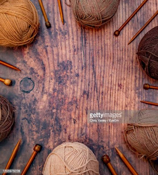 flat lay of brown balls of knitting yarn and bamboo knitting needles on a hardwood floor - needlecraft stock pictures, royalty-free photos & images