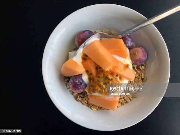 flat lay of cereals with fresh tropical fruits in a bowl - rafael ben ari - fotografias e filmes do acervo