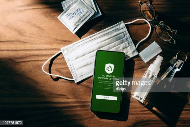 flat lay of daily essential during pandemic, with surgical face mask, disinfectant sanitizer spray, alcohol wipes and smartphone on wooden table. covid-19 contact tracing app on smartphone display showing that the user is safe from coronavirus infection - antiseptic wipe stock pictures, royalty-free photos & images
