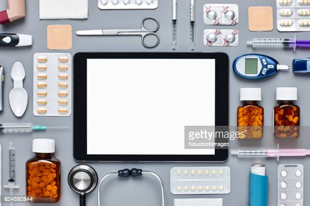 Flat lay of digital tablet surrounded with various medical equipment
