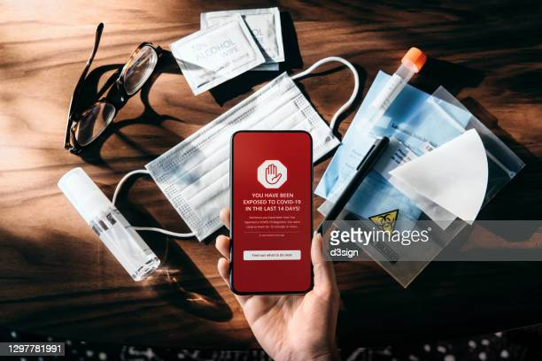 flat lay of essential during pandemic, with surgical mask, sanitizer and alcohol wipes on table. woman's hand holding smartphone with covid19 contact tracing app showing the user have been exposed to coronavirus, conducting deep throat saliva test at home - antiseptic wipe stock pictures, royalty-free photos & images
