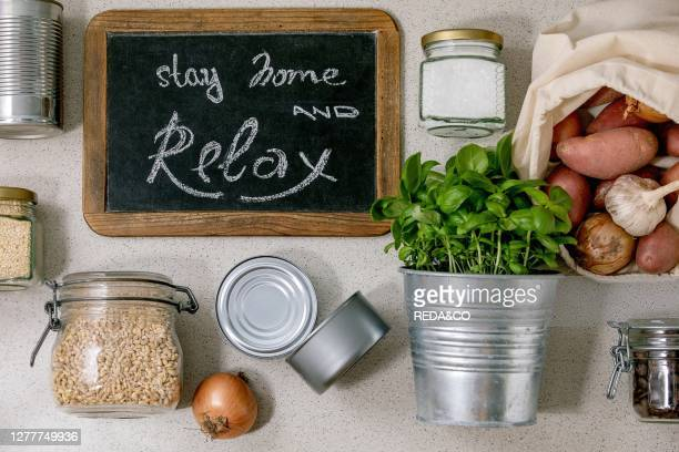 Flat lay of food supplies crisis for quarantine isolation period. Different glass jars with grains. Cans of canned food. Vegetables. Chalkboard...