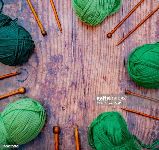 flat lay of green balls of knitting yarn and bamboo knitting needles on a hardwood floor - needlecraft stock pictures, royalty-free photos & images