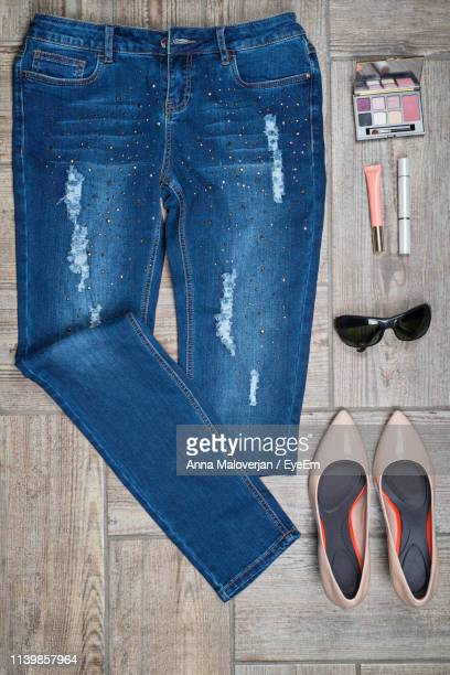 flat lay of jeans with make-up and personal accessories on wooden floor - womenswear stock pictures, royalty-free photos & images