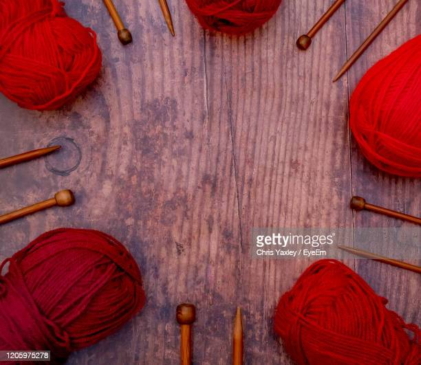 flat lay of red balls of knitting yarn and bamboo knitting needles on a hardwood floor - needlecraft stock pictures, royalty-free photos & images