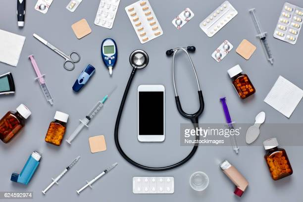 Flat lay of smart phone surrounded with various medical equipmen