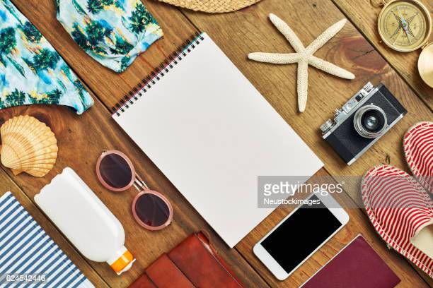 Flat lay of spiral notebook surrounded with beach travel accessories