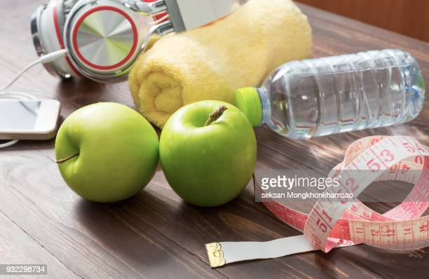Flat lay of Sport equipment. Sneakers, dumbbells, water, towel, fruits and phone on white background. View from above