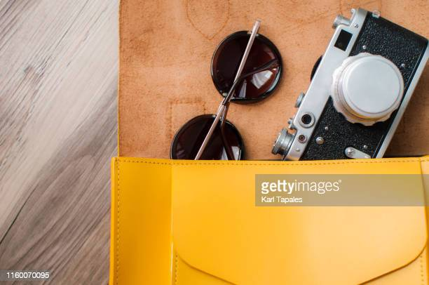 flat lay of yellow leather bag for woman, vintage camera and sunglasses on a wooden table - capital region stock pictures, royalty-free photos & images