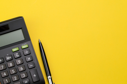 Flat lay or top view of black pen with calculator on vivid yellow background table with blank copy space, math, cost, tax or investment calculation 924620660