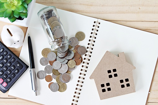 Flat lay or top view of wood house model and coins scattered from glass jar on open blank notebook paper 840393626