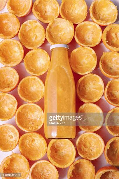 flat lay orange juice in a bottle and the orange peels squeezed arranged around the bottle - 果肉 ストックフォトと画像