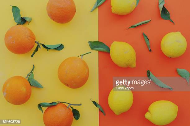 flat lay organic oranges and lemons in a colorful background - naranja fotografías e imágenes de stock