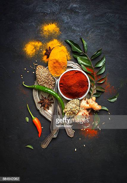 flat lay overhead view herb and spices on textured black background. - curry meal stock pictures, royalty-free photos & images