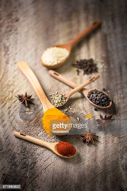 Flat lay overhead view herb and spices with wooden spoon on rustic wooden background.