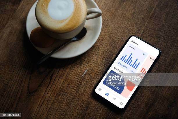 flat lay shot of managing bank account online with smartphone - table stock pictures, royalty-free photos & images