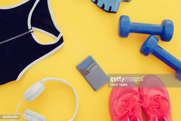 Flat lay shot of woman Sport equipment, shoes, water, earphone and phone on yellow background