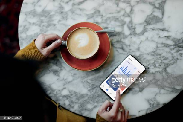 flat lay shot of young woman managing bank account online with smartphone - merchandise stock pictures, royalty-free photos & images