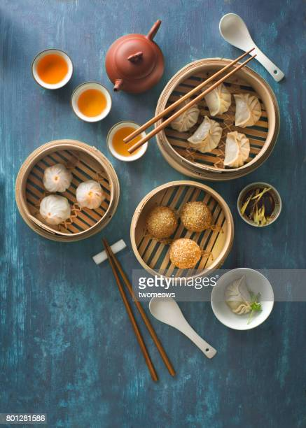 Flat lay traditional Chinese food dim sum on blue rustic table top.