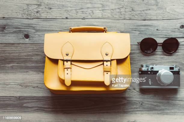 flat lay travel concept with a yellow leather shoulder bag, a vintage camera and a pair of sunglasses - shoulder bag stock pictures, royalty-free photos & images