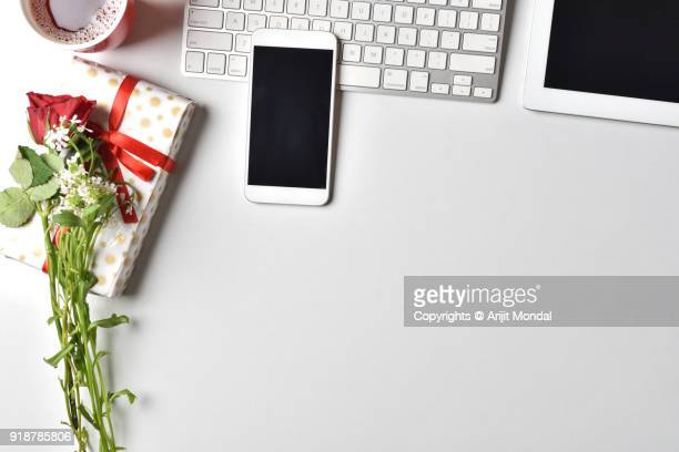 Flat lay Valentines day background with smartphone, tablet, computer keyboard, gift top view copy space