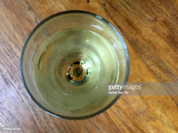 flat lay view of a glass of white wine on a wooden table in a bar/ restaurant. - rafael ben ari bildbanksfoton och bilder