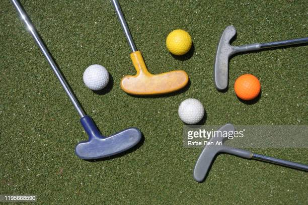 flat lay view of mini golf clubs and balls - rafael ben ari stockfoto's en -beelden