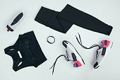 flat lay with sportswear with sneakers, fitness tracker and sports bottle isolated on grey