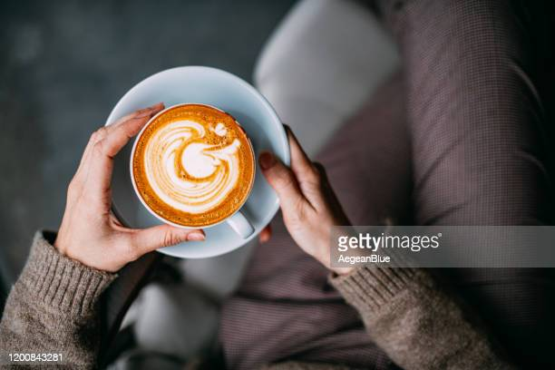 flat lay woman hand holding coffee latte - coffee stock pictures, royalty-free photos & images