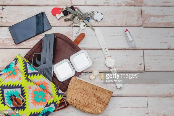 flat lay  woman´s bag with  gun and feminine items