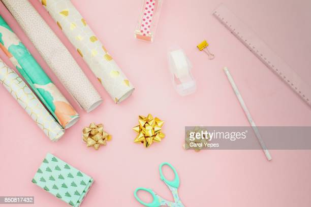 flat lay wrapping christmas gifts in pink
