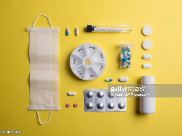 flat layer with various types of pills, capsules, a surgical mask, a test tube and medical supplies on yellow background. - 抗ウイルス薬 ストックフォトと画像