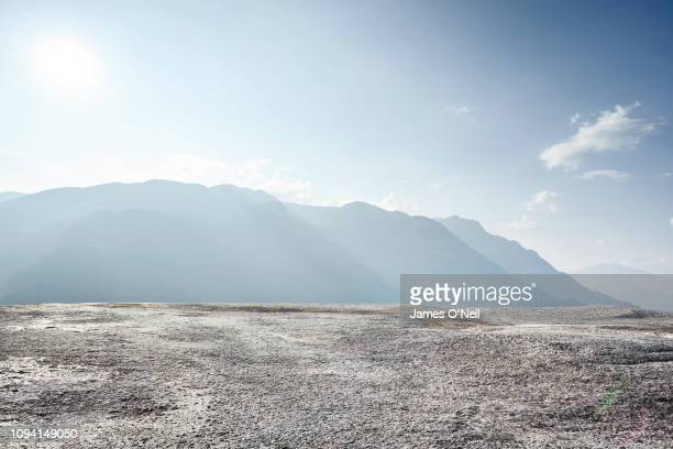 flat rocky plateau with distant mountains and sunlight - fels stock-fotos und bilder