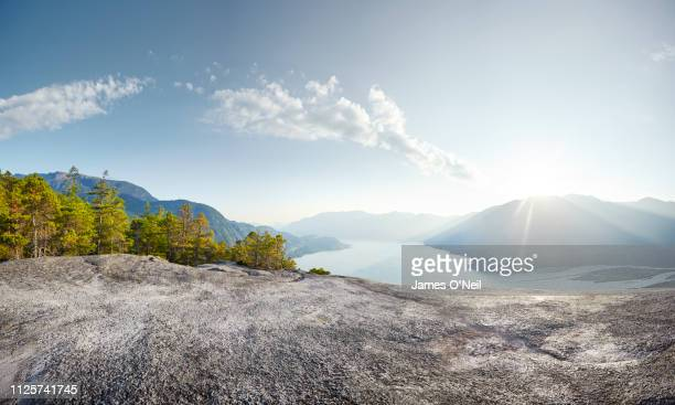 flat rocky plateau with forests and distant mountains basked in sunlight - rock stock pictures, royalty-free photos & images