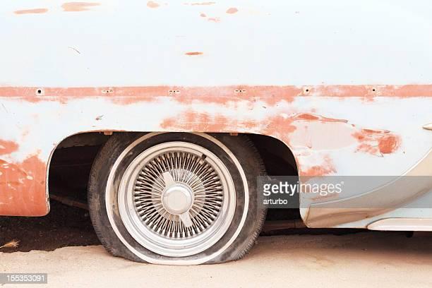 Un pneu sur rusty épave de voiture