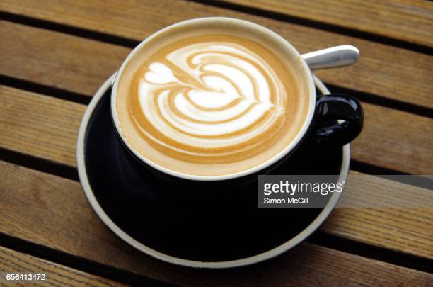 Flat white coffee in a black cup and saucer on a wood-slatted cafe table
