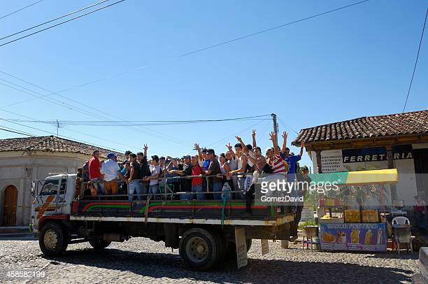 Flatbed Truck Loaded with People Driving Down Street