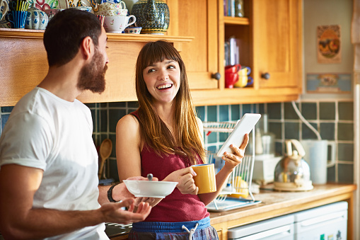 Flatmates laughing about something on a tablet PC - gettyimageskorea
