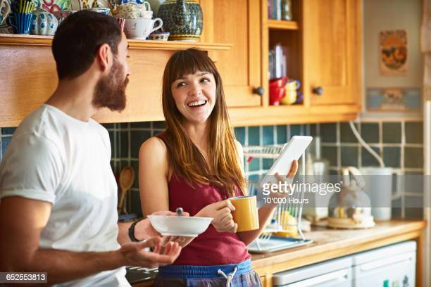 flatmates laughing about something on a tablet pc - roommate stock pictures, royalty-free photos & images
