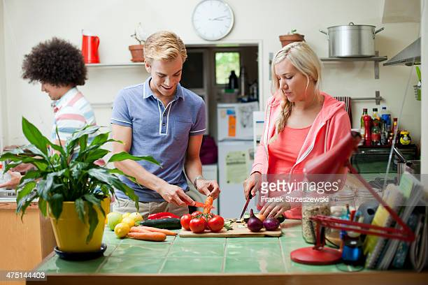 Flatmates preparing vegetables in kitchen