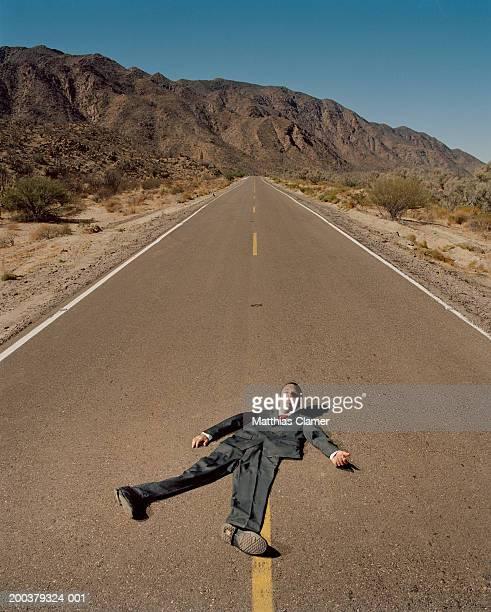 Flattened businessman on road, smiling, portrait (digital composite)