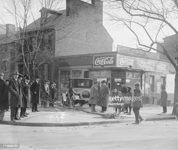A flattened tree and a car's position on the sidewalk is evidence of an accident that occurred on a street corner early twentieth century