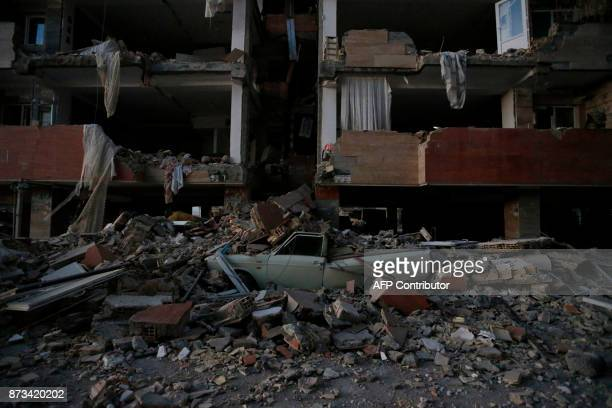 TOPSHOT A flattened vehicle underneath building rubble is seen following a 73magnitude earthquake at Sarpole Zahab in Iran's Kermanshah province on...