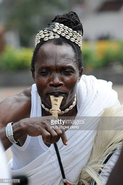 A flautist dances along with Eyo masquerades during the celebration of Eyo festival in Lagos on November 26 2011 The Adamu Orisa play otherwise known...
