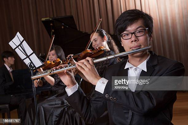 flautist holding and playing the flute during a performance, looking at the camera - pianist front stock pictures, royalty-free photos & images
